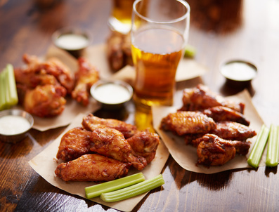 different flavored chicken wings on wax paper served with beer, ranch dressing and celery sticks